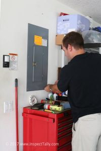 Four point inspector accessing electrical panel.