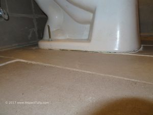 Home inspector identifies toilet that has been reset but not re-caulked properly after bathroom had been re-tiled.