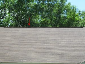 The home inspector identifies properly installed ridge cap and shingles on roof of home curling roof shingles.