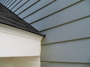 Exterior view of a roof to wall intersection where kick out flashing was needed, discussed in a home inspection report.