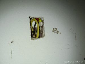 Discovered during a home inspection in Havana, FL is an improper wire splice partially enclosed in the wall, showing the missing junction box