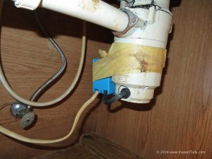During a Crawfordville, FL home inspection, a junction box is shown improperly secured with TAPE to the garbage disposal.